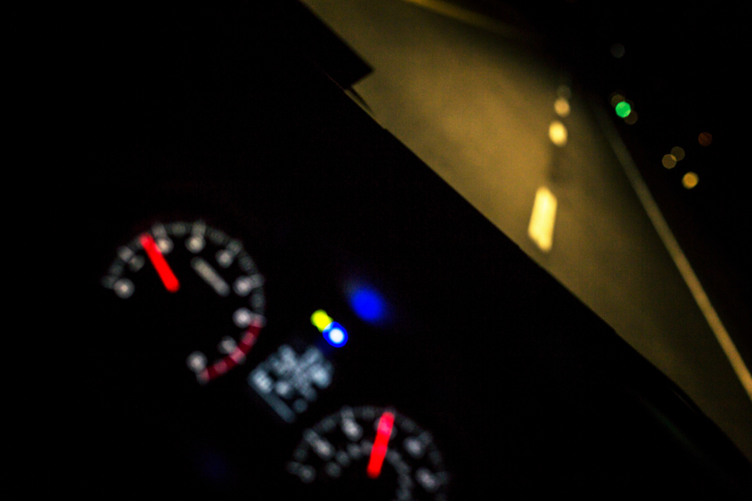Tilted view of an illuminated car interior dashboard display, with various graphic icon lights, and large blurred tachometer and speedometer gauges. The car's headlights illuminate the road ahead through the windshield above the dashboard. In this vehicle, tachometer, speedometer, odometer, fuel gauge and most other needed information is computer generated electronically, and digitally displayed.